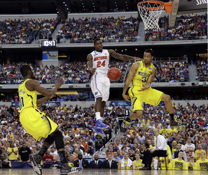 Michigan's Trey Burke (3) passes the ball to Tim Hardaway Jr. (10) in front of Florida's Casey Prather (24) during the second half of Sunday's NCAA college basketball tournament in Arlington, Texas.