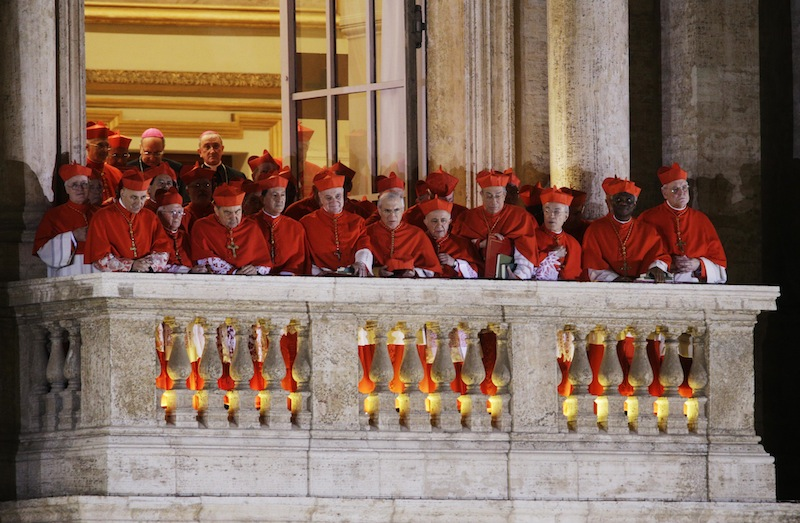 Cardinals watch as Pope Francis speaks to the crowd from the central balcony of St. Peter's Basilica at the Vatican, Wednesday, March 13, 2013. Cardinal Jorge Bergoglio, who chose the name of Francis, is the 266th pontiff of the Roman Catholic Church. (AP Photo/Andrew Medichini)