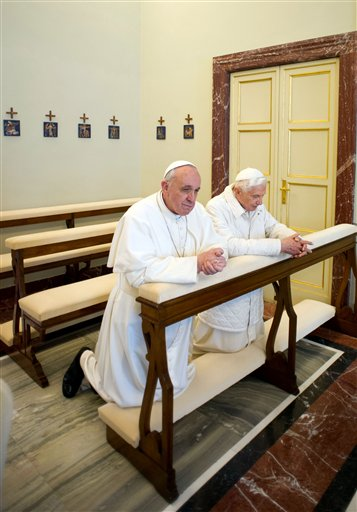 In this photo provided by the Vatican paper L'Osservatore Romano, Pope Francis, left, and Pope emeritus Benedict XVI pray together in Castel Gandolfo Saturday. Pope Francis has traveled to Castel Gandolfo to have lunch with his predecessor Benedict XVI in a historic and potentially problematic melding of the papacies that has never before confronted the Catholic Church.