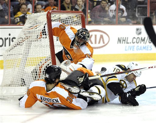 Philadelphia Flyers goalie Ilya Bryzgalov (30), of Russia, watches Oliver Lauridsen (38), of Denmark, and Boston Bruins' Nathan Horton (18) collide in front of the goal in the first period of an NHL hockey game, Saturday, March 30, 2013, in Philadelphia. The Flyers won 3-1. (AP Photo/Michael Perez)