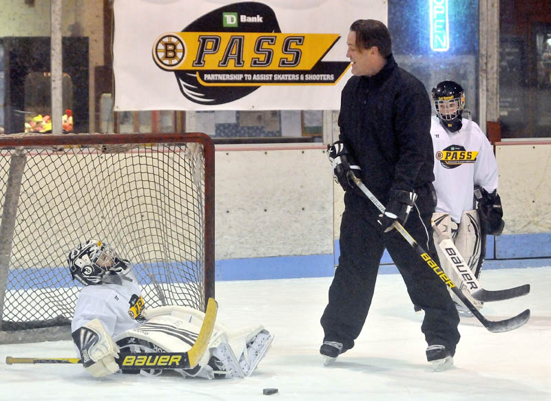 SEE WHAT I MEAN: Former Boston Bruin Bruce Shoebottom helps goalie Joshua Girard, 9, with his technique during a clinic Tuesday at Sukee Arena in Winslow. The Boston Bruins alumni association hosted the clinic with players from Central Maine Youth Hockey Association.