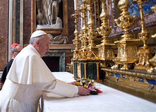 In this photo provided by the Vatican newspaper L'Osservatore Romano, Pope Francis puts flowers on the altar inside St. Mary Major Basilica in Rome on Thursday.