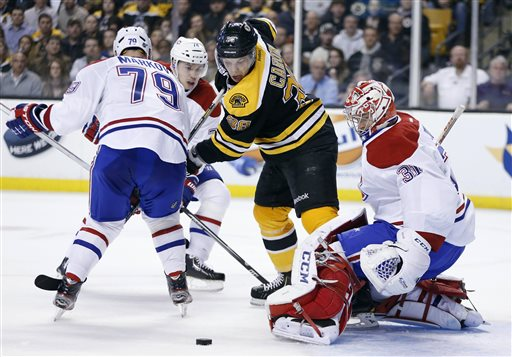 Boston Bruins' Jordan Caron (38) tries to control the puck in front of Montreal Canadiens' Carey Price (31) as Canadiens' Andrei Markov (79), of Russia, defends in the second period of an NHL hockey game in Boston, Wednesday, March 27, 2013. (AP Photo/Michael Dwyer)