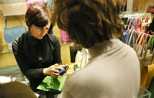 A salesperson at Barneys New York uses an iPod Touch to record a customer's purchase. Led by the Apple example at all of its stores, more retailers are ditching clunky registers while freeing up space and salespeople.