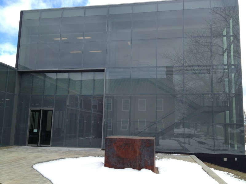 The exterior of the Alfond-Lunder Family Pavilion at the Colby College Museum of Art, with the college's older architecture reflected.