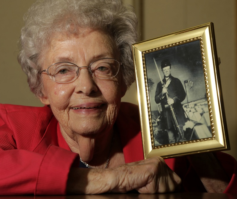 Juanita Tudor Lowrey, age 86, poses with a photo of her father, Civil War veteran Hugh Tudor Tuesday, March 19, 2013, in Kearney, Mo. Lowrey received pension benefits related to her father's Civil War service until she was 18 after her father died when she was 2 years old. (AP Photo/Charlie Riedel)