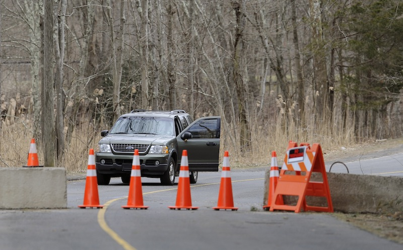 A guard stands watch behind cones and concrete barrier at the entrance to Sandy Hook Elementary School in Newtown, Conn., Thursday, March 28, 2013. Search warrants released Thursday, March 28, 2013, revealed that an arsenal of weapons including guns, more than a thousand rounds of ammunition, a bayonet and several swords was seized at Adam Lanza's home. Lanza killed his mother, Nancy Lanza in their home before he forced his way into Sandy Hook Elementary School in Newtown, Conn, killing 26 people. (AP Photo/Jessica Hill)