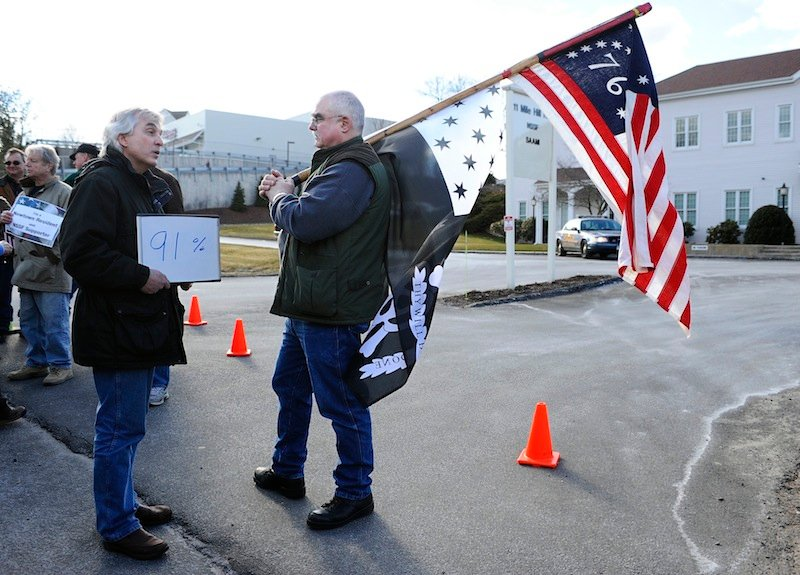 John Woodall. left, of Newtown, Conn., carries a sign that he says indicated the percentage of Americans who support universal background checks speaks with Gordon Jones of Southbury, Conn., a supporter of gun rights during a rally outside the National Shooting Sports Foundation headquarters in Newtown Thursday, March 28, 2013. Search warrants released Thursday, March 28, 2013, revealed that an arsenal of weapons including guns, more than a thousand rounds of ammunition, a bayonet and several swords was seized at Adam Lanza's home. Lanza killed his mother, Nancy Lanza in their home before he forced his way into Sandy Hook Elementary School in Newtown, Conn, killing 26 people. (AP Photo/Jessica Hill)