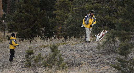 Searchers use a dog Wednesday to search the area around the Monument, Colo., home of Colorado Department of Corrections Executive Director Tom Clements, who was shot and killed Tuesday evening.