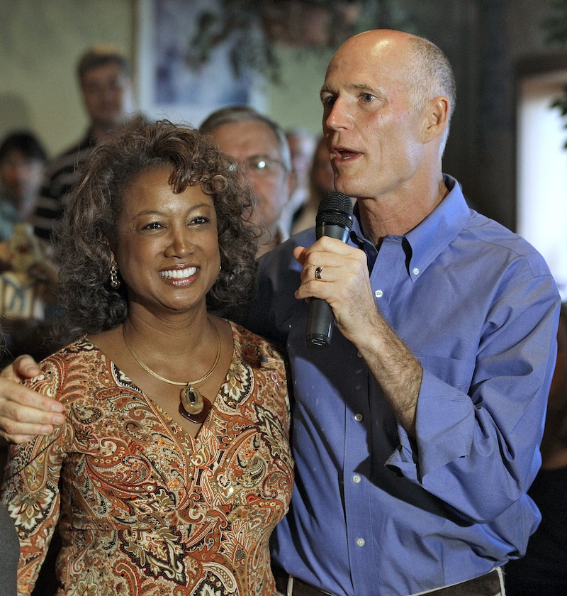 In this Oct. 26, 2010 file photo, Florida Republican gubernatorial candidate Rick Scott, right, puts his arm around running mate Rep. Jennifer Carroll, R-Jacksonville, during a campaign stop in New Port Richey, Fla. Carroll abruptly resigned Wednesday, March 13, 2012 after authorities questioned her ties into internet cafes that authorities say are fronts for gambling. (AP Photo/Chris O'Meara, File)