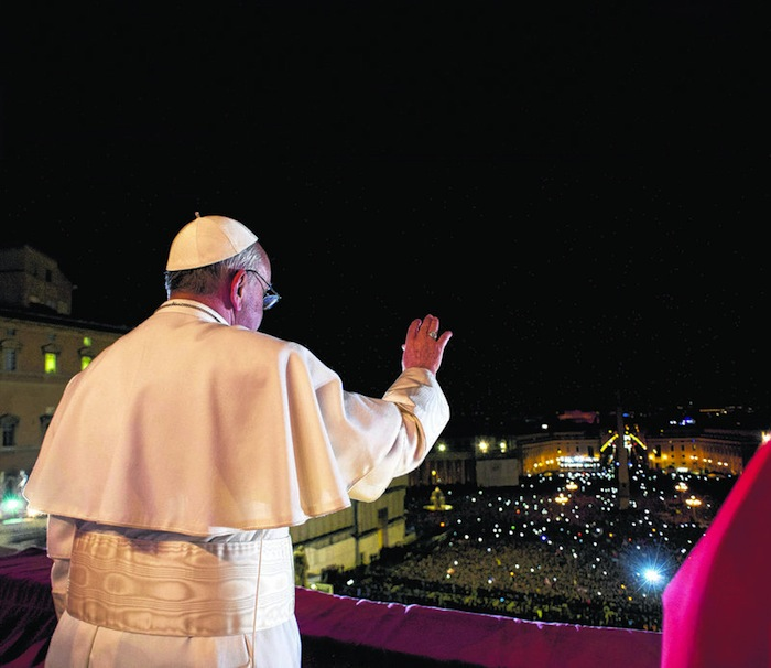 Pope Francis waves to the crowd from the central balcony of St. Peter's Basilica at the Vatican in a photograph released by Osservatore Romano at the Vatican, March 13, 2013. (AP Photo/L'Osservatore Romano)
