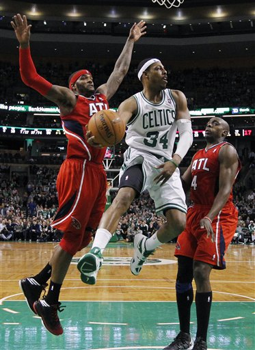 Boston Celtics' Paul Pierce (34) passes off between Atlanta Hawks' Josh Smith, left, and Anthony Tolliver (4) during the second half of NBA basketball game in Boston, Friday, March 8, 2013. The Celtics won 107-102 in overtime. (AP Photo/Michael Dwyer)