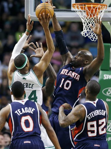 Atlanta Hawks' Johan Petro (10) blocks a shot by Boston Celtics' Paul Pierce (34) during the first quarter of an NBA basketball game in Boston, Friday, March 29, 2013. (AP Photo/Michael Dwyer)