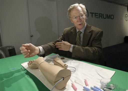 Atlanta cardiologist Dr. Spencer King demonstrates how doctors can open blocked heart arteries by going through an arm, using a model, at the American College of Cardiology conference in San Francisco recently.