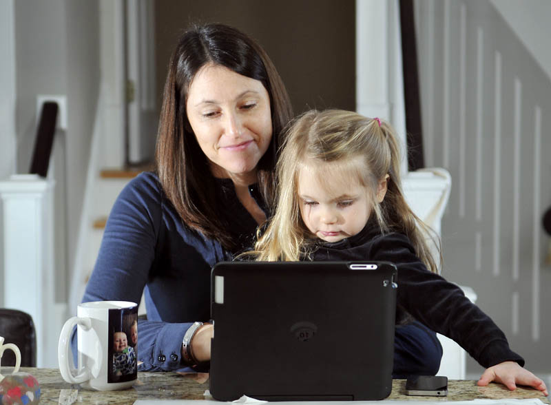 Emily Bessey holds her daughter, Daisy, 3, while blogging at their Hallowell home earlier this month. The elder Bessey has been writing online about her infant son, Ezra, and the affliction that claimed his life, spinal muscular atrophy.
