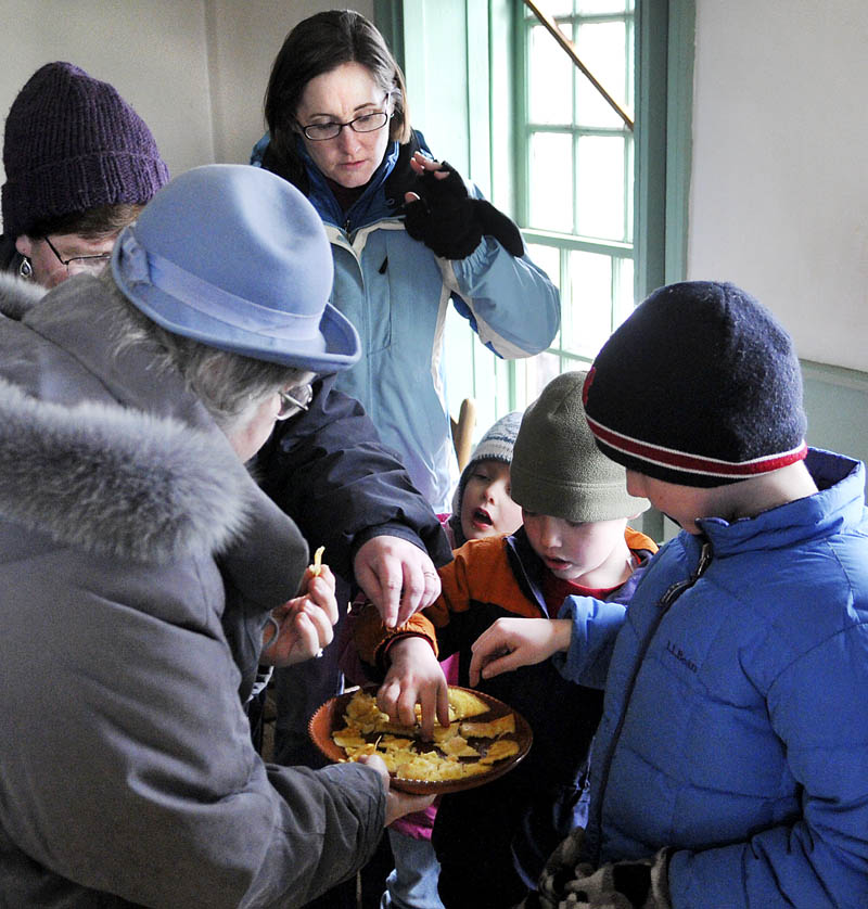 Old Fort Western guests sample cornbread cooked in a fireplace at the historic landmark, on the banks of the Kennebec River, on Sunday in Augusta, during Maple Syrup Sunday festivities. Visitors learned about tapping maple trees with sumac, evaporating sap in kettles and the food consumed by early settlers of the Kennebec valley.