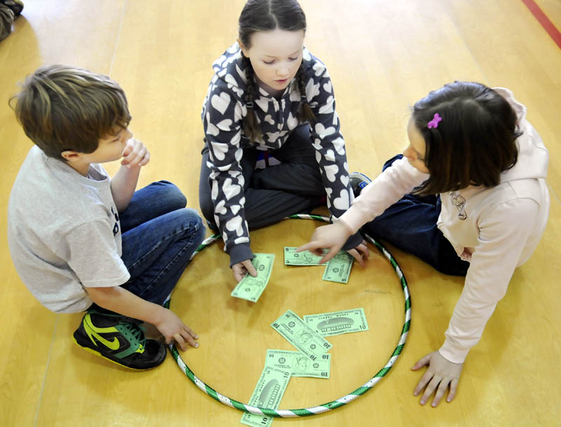 Whitefield Elementary School Sullivan Anderson, Miranda Northrup, center, and Abby Peaslee count money they collected Tuesday during physical education class.