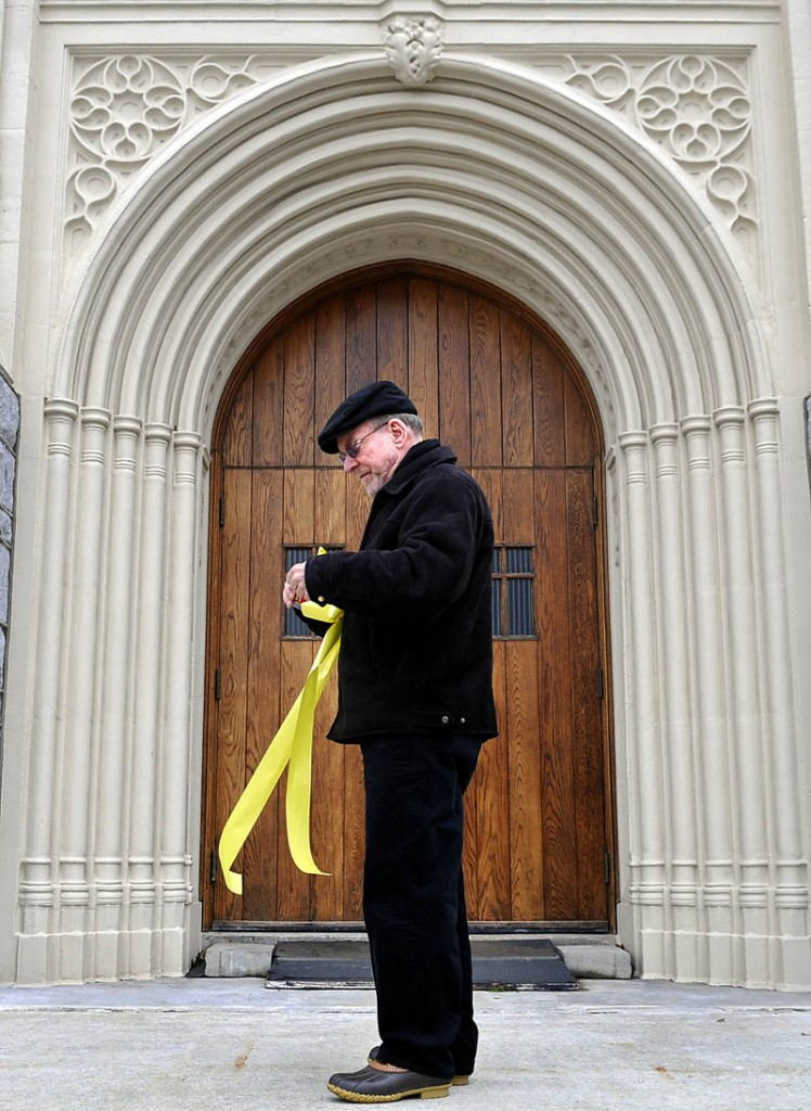 Rev. Francis Morin hangs a ribbon on the entrance of St. Mary's Catholic Church in Augusta Wednesday, moments after the announcement of a new pope. Jorge Bergoglio, 76, of Argentina, was elected pope and chose the name Francis, becoming the first pontiff from the Americas and the first from outside Europe in more than a millennium.