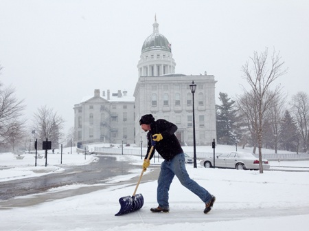 Tim Campbell shovels snow at the State House complex on Tuesday in Augusta. He was part of the Bureau of General Services crew clearing sidewalks and lots.