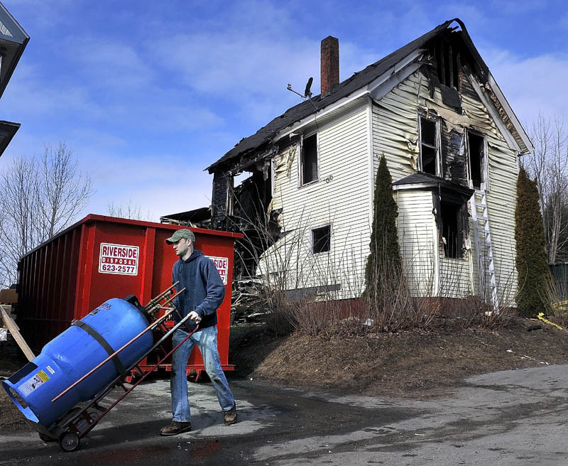 Rob Gay carts a boiler mate from the remains of 146 Northern Ave. in Augusta Monday, as crews raze the apartment building destroyed by fire on Thursday. Scott Laliberte, proprietor of Riverside Disposal, said the building would be down and removed by Tuesday, with the foundation filled in. Gay and other heating contractors removed the heating system from the building, to be installed in another building.