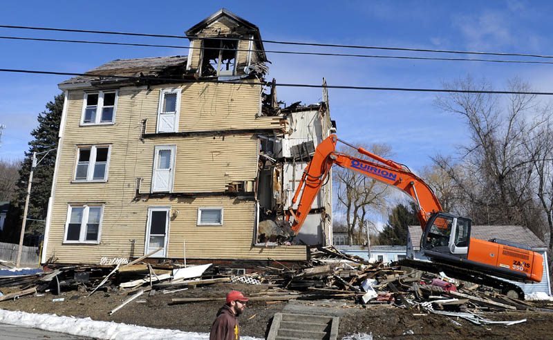 An excavator razes an apartment building at 1 Penobscot St. in Augusta Monday The four-story building was destroyed by fire Jan. 29.