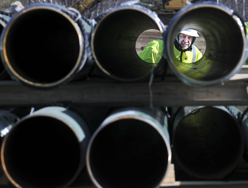 Rick Bellemare inspects a steel pipe delivered to the Windsor laydown yard of Maine Natural Gas on Monday. The firm, competing to deliver gas to Kennebec County, expects to start installing pipes in Windsor to connect a line to Augusta. Bellemare works for Enterprise Trenchless Technologies of Lisbon Falls.