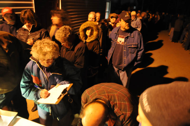 Pittston residents line up in the cold Thursday evening to sign petitions to recall selectmen following the termination of Ann Chadwick, 75, from town positions.