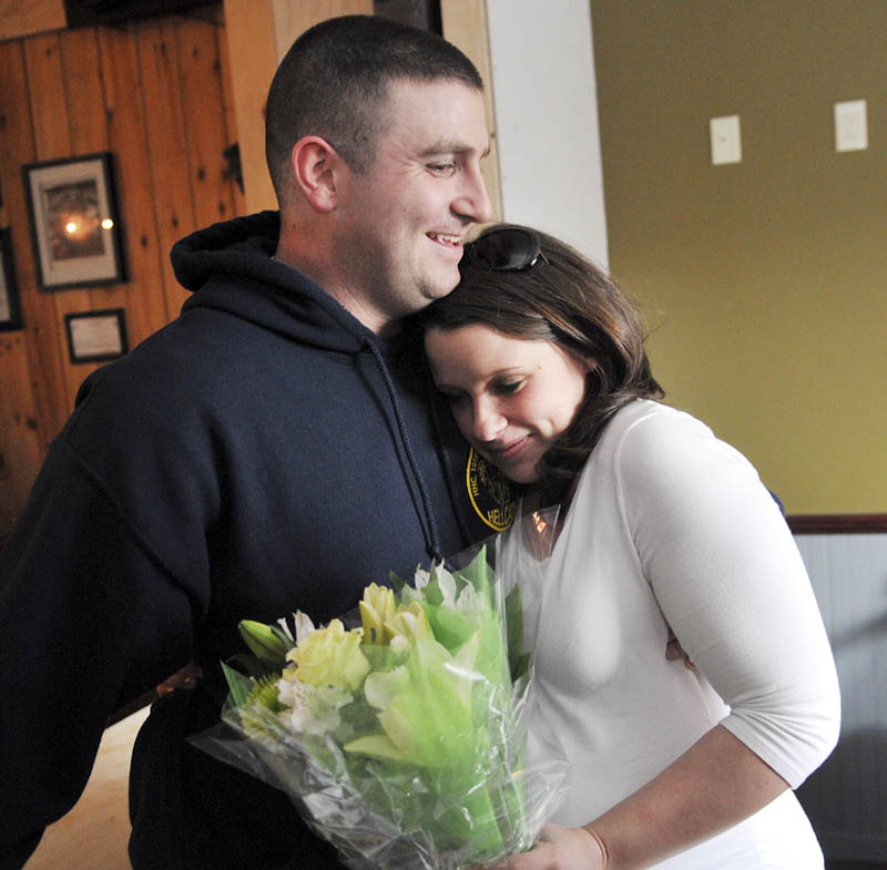 Megan McGuire hugs her husband, Travis, on Wednesday, moments after he surprised her by returning early from an Army deployment in Afghanistan, to be present for the birth of their first child. Travis McGuire walked into the Depot Sports Bar in Gardiner and gave his wife a bouquet of flowers as she dined with family and friends.