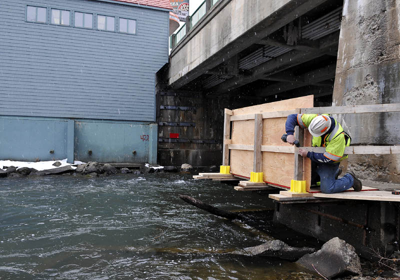 Maine Department of Transportation worker Keith Bates erects a railing on a platform, attached to a pier suspending the bridge spanning Cobbossee Stream, on Bridge Street in Gardiner Monday. Crews will be replacing concrete in the pier for the next four to six weeks, according to bridge maintenance supervisor George James.