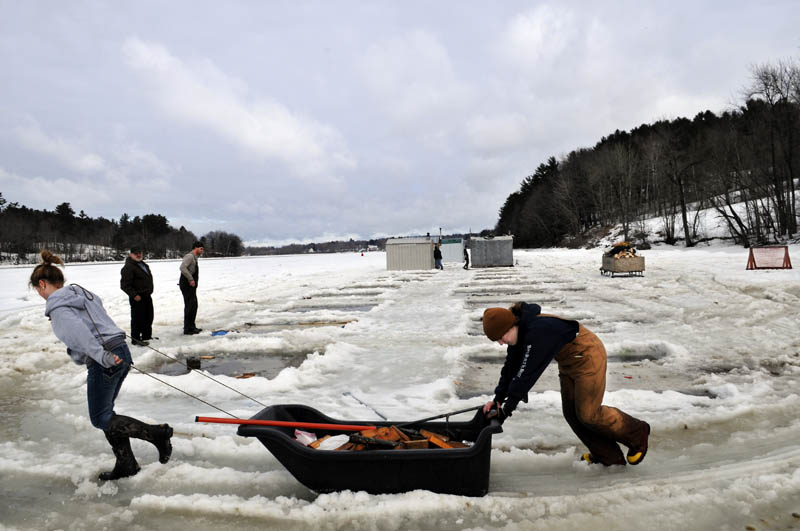 Airyn Jewett, left, and Kate Baker, both 14, haul a sled full of wood blocks they chiseled out of the Kennebec River Sunday, while removing shacks at Baker's Smelt Camps in Pittston. Friends, neighbors and employees helped proprietor Mike Baker remove the fishing shacks, rented to anglers by the tide, after the ice became brittle over the weekend. The wood that balanced the shacks over race holes for the winter.