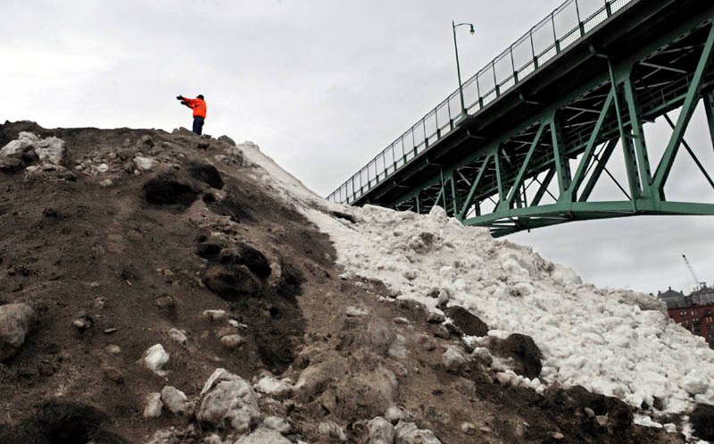 Augusta Public Works employee Matt Jackson directs a truck to pour snow Thursday on the winter dump located on the banks of the Kennebec River, on the east side of Augusta. Workers were collecting snow from city schools and relocating it to the hill that rises to a height just below the catwalk underneath Memorial Bridge. The hill isn't as high as it has been in past winters, workers said, and usually melts by the end of spring.