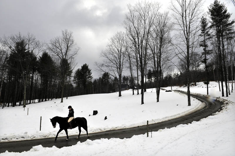 """Kelsey Stinneford, of Wayne, leads her horse beneath overcast skies Tuesday, down a lane in Wayne while riding back to the Taylor Farm in Fayette, where she stables the steed. A competitive rider on the dressage team at Post University in Connecticut, Stinneford said the wet conditions do not deter her from riding. """"This is how I choose to spend my spring break,"""" she said."""