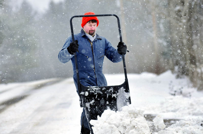 "Kyle Smith kicks loose a bucket of snow Tuesday while clearing the drive of his West Gardiner home. ""A year ago we were riding horses in T-shirts,"" Smith recalled, while collecting this winter's most recent deposit of snow."