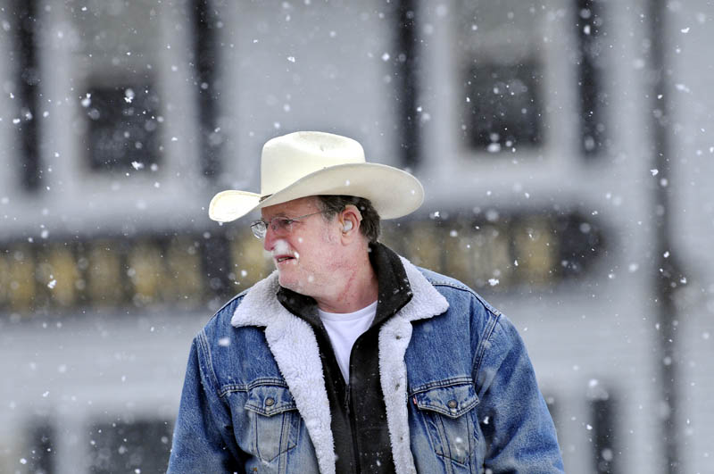 Lewis Armstrong, of Augusta, walks through Memorial Circle in Augusta on Monday during a snow shower.