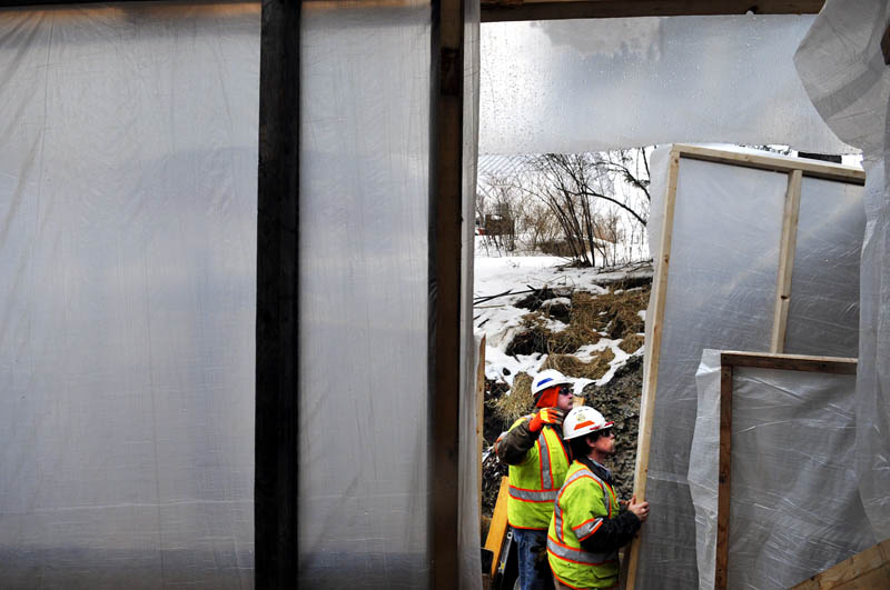 Maine Department of Transportation workers Dave Ferland, left, and Lenny Sioch hang plastic tarp frames with colleagues Tuesday on a platform beneath the bridge on Route 41, spanning Mill Stream in Vienna. The workers were erecting a winter enclosure to commence repairing posts, rails and wing walls on the bridge, according to Ferland, the supervisor. The crew should be finished fixing the span in about six weeks.