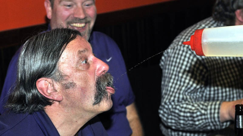 Ron Webber gulps down squirts of sake from chef Jerry Lin, at Mirakuya Steak House in Waterville Wednesday night.