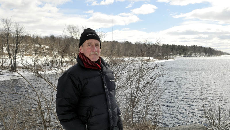 Peter Garrett, president of the Kennebec-Messalonskee Trails, stands on the bridge abutment at the southern end of the Rotary Centennial trail in Winslow on Saturday. Land recently donated for trail use by Madison Paper Industries appears in the background, along the shore of the Kennebec River on the Winslow side.