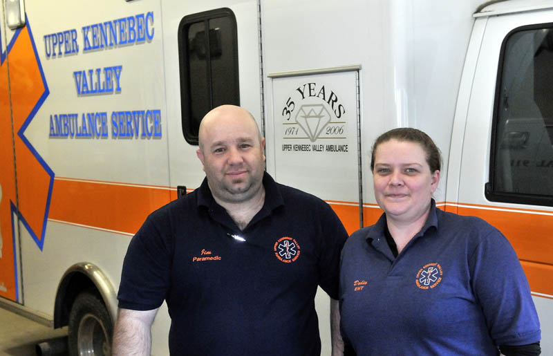 """James Baldwin, a paramedic, and Doraine """"Dodie"""" Mathieu, an emergency medical technician, both with the Upper Kennebec Valley Ambulance Service, stand next to an ambulance at the service's Bingham office Friday."""