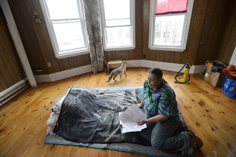 Katrina LaCourse 47, of Lewiston, looks over paperwork in her apartment Wednesday. LaCourse was recently removed removed from the city's General Assistance welfare rolls.