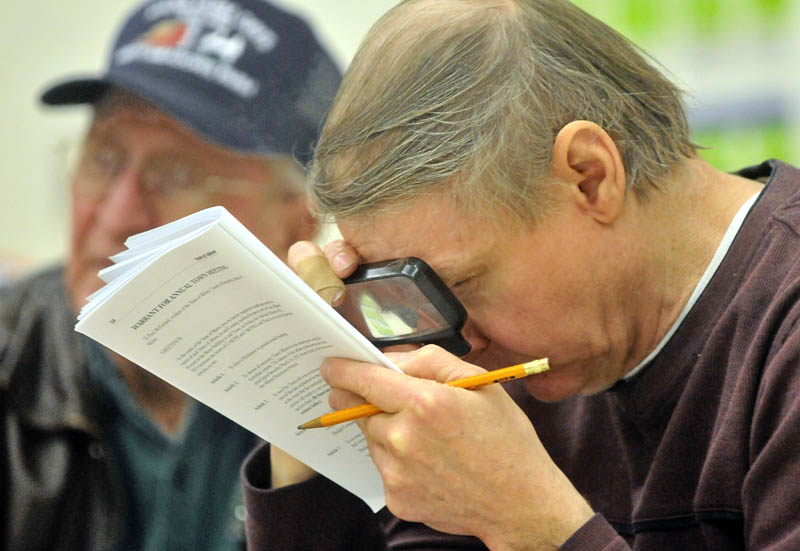 Deane Mason takes a close look at the articles up for vote during the annual Town Meeting at the Albion Elementary School Saturday.