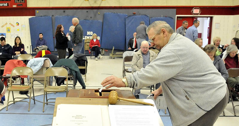 Nelson Harding, 69, places his vote for Article 3 in to the ballot box during the annual Town Meeting at the Albion Elementary School Saturday.