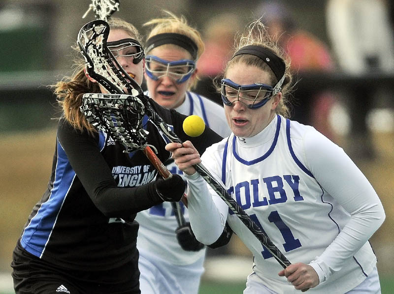 STICK WORK: University of New England's Cassidy Ruocco,left, and Colby's Abby Hatch battle for the ball in the first period Saturday at Colby College in Waterville. The Mules won 18-0.