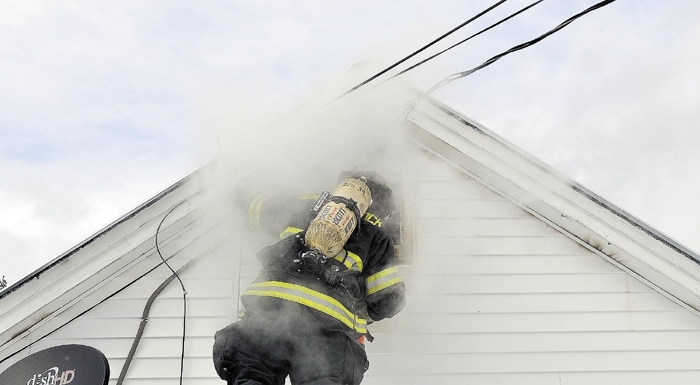 Nicholas Quimby, a firefighter with Norridgewock cuts a hole in the wall while battling a house fire at 567 Norridgewock Rd in Fairfield Wednesday afternoon.