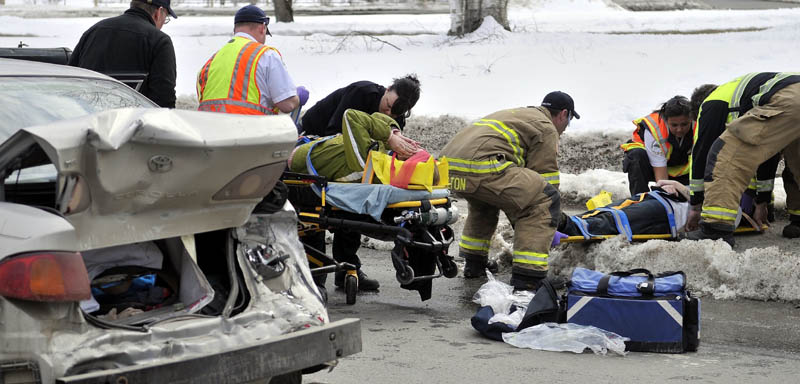 Rescue workers from the Waterville Fire Department, Delta Ambulance and Waterville Police dDepartment tend to people injured in an accident on Upper Main Street Friday afternoon.