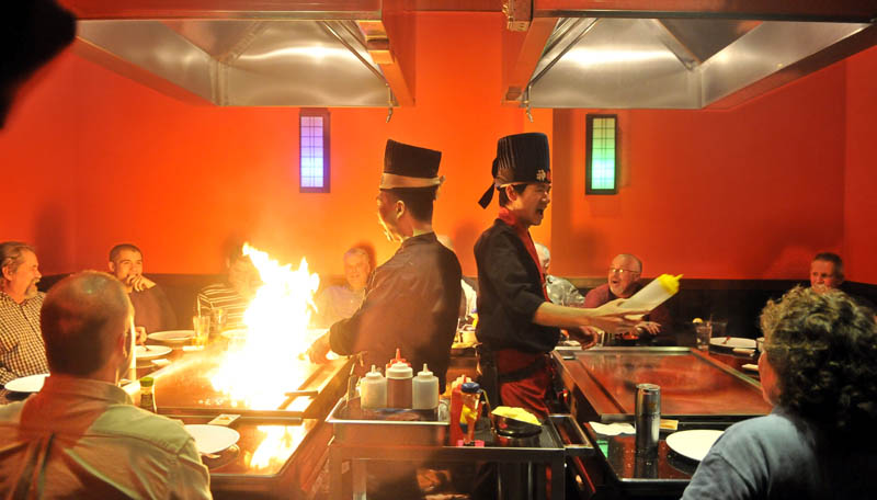 Chef Jerry Lin, left, heats up the hibachi as chef Ricky Huang squirts sake in to diners' mouths during an entertaining exhibition of culinary skills for a group of diners at Mirakuya Steak House in Waterville Wednesday night.