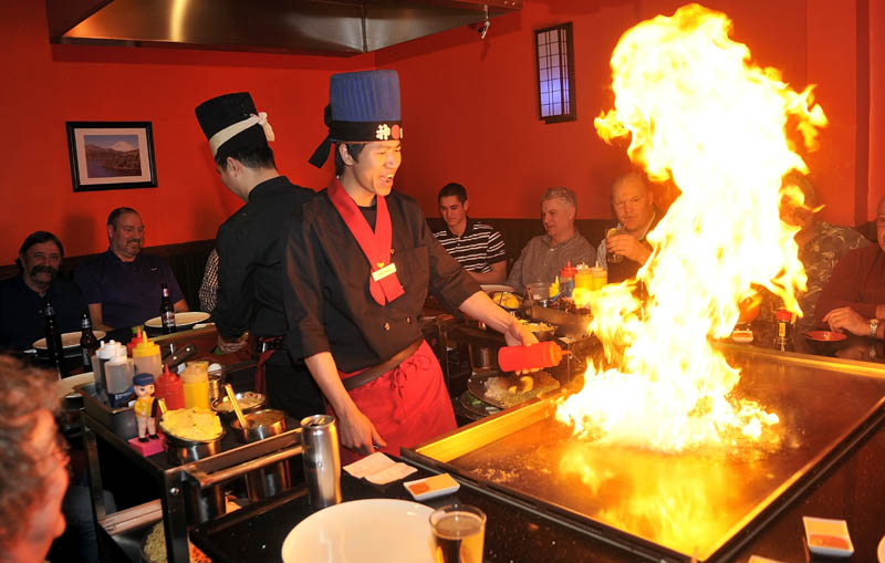 Chef Ricky Huang, right, fires up the hibachi as he prepares dinner for a group of diners at Mirakuya Mirakuya Steak House, at 150 Kennedy Memorial Drive in the JFK Plaza in Waterville, Wednesday night.