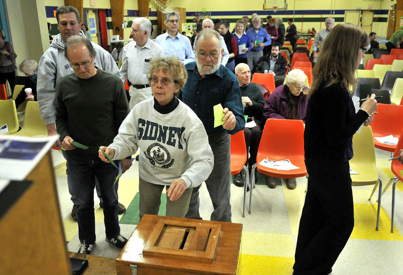 Nancy Robbins, of Sidney, casts her written ballot for a vote on budget committee members during the annual town meeting at the James H. Bean School Saturday.