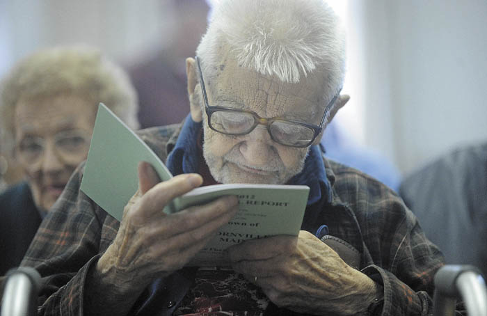 Cornville's oldest resident, Laurence Amazeen, 98, skims through the town's annual report before the start of the Town Meeting at Town Hall Saturday morning.