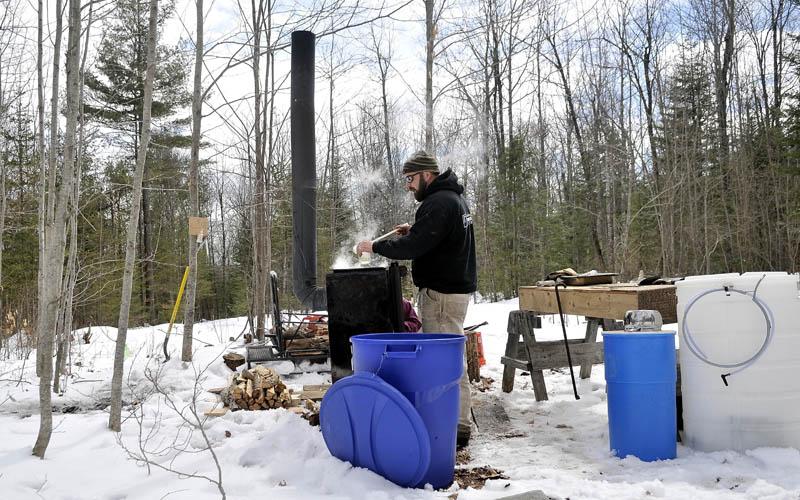 Nate Smart pours a sample of syrup at his friends' Axtell Road residence in Oakland Saturday. Smart and his friend, Bruce Marshall, planned to spend the weekend harvesting maple syrup.