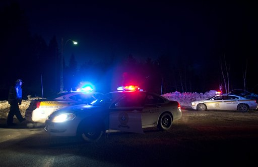 Police vehicles block a road just outside the town of Chertsey, Quebec on Sunday night, during a search for escaped prisoners. At least one escapee was tracked down hours after he fled.